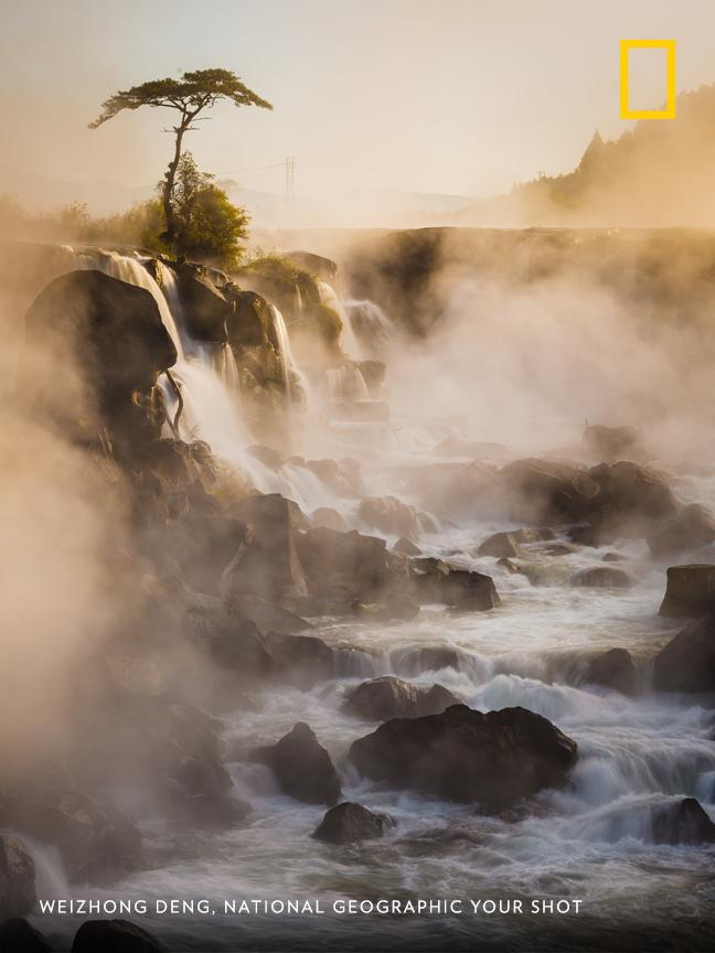 """When the sun rose,"" writes photographer Weizhong Deng, ""it lit up the falls beautifully and cleared away some of the mist."" https://on.natgeo.com/2D8F0Se"