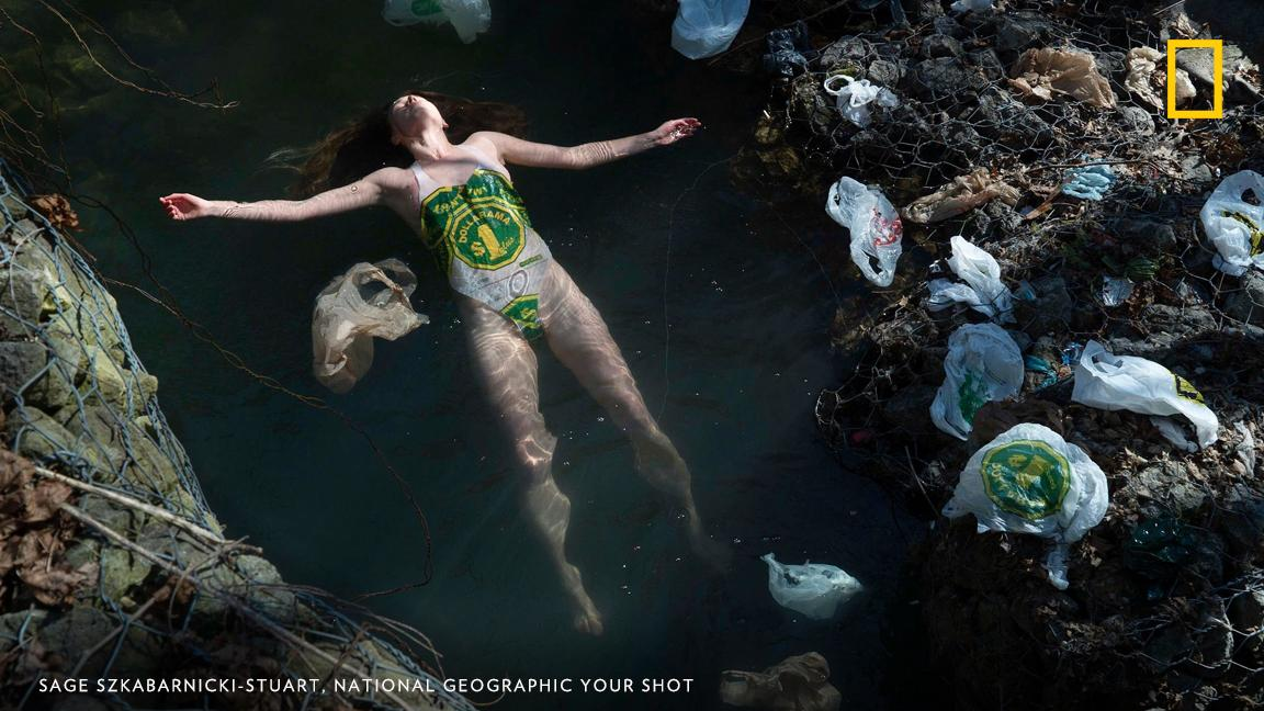 "In Toronto's High Park, a stream littered with plastic bags. ""In this image I am wearing a swimsuit I made with plastic bags found along the stream,"" writes Your Shot photographer Sage Szkabarnicki-Stuart. ""After I die, my waste will outlive me."" On World Environment Day, take the pledge to reduce single-use plastic in your life: https://on.natgeo.com/2IoPE92"