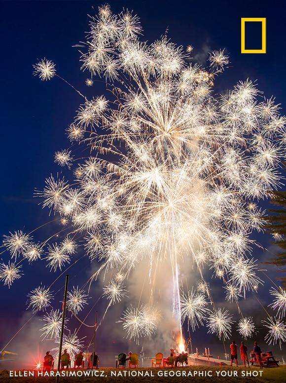 "Sparks fly in this red, white, and blue moment captured by Your Shot photographer Ellen Harasimowicz during a backyard 4th of July celebration. ""Watching the fireworks explode in the sky and fall into the water just a few feet away is breathtaking,"" she writes. https://on.natgeo.com/2XjkcP6"